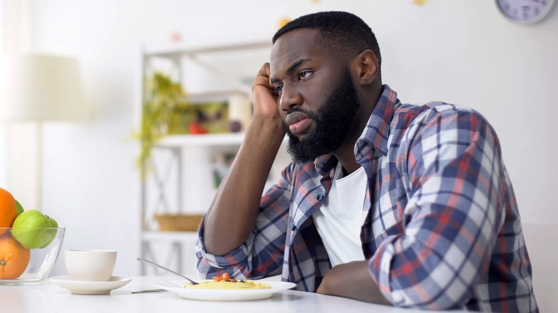 a man not eating a bowl of food in front of him because he has a loss of appetite due to anxiety
